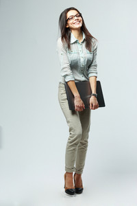 Full-length portrait of a young happy businesswoman holding laptop on gray background