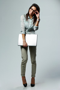 Full-length portrait of a young smiling businesswoman holding laptop on gray background