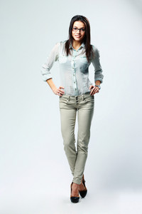 Full-length portrait of a young smiling businesswoman standing on gray background