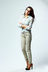 Full-length portrait of a young smiling woman with arms folded isolated on gray background