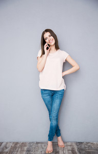 Full length portrait of a young woman talking on the phone