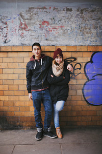 Full length portrait of handsome young man standing with his beautiful girlfriend leaning against a wall. Mixed race teenage couple posing together outdoors