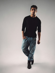 Full length portrait of stylish young man in casuals looking at camera. Hispanic male model posing on grey background.