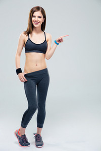 Full length portrat of a smiling sporty woman pointing finger away over gray background. Looking at camera