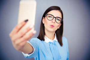 Funny businesswoman making selfie photo