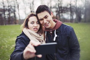 Funny teenage couple photographing themselves with smart phone in the park.  Cute young girl with her boyfriend taking self portrait with cell home outdoors.