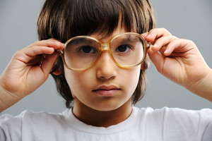 Geeky little boy studying and wearing glasses