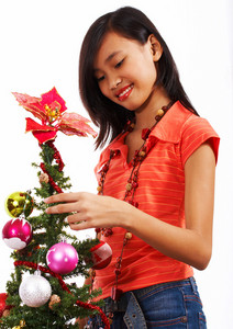 Girl Adding Tinsel To A Christmas Tree