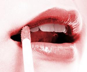 Girl Applying Red Lip Gloss To Her Lips