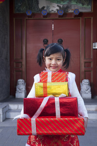 Girl holding gifts dressed in holiday attire