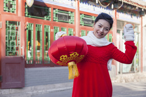 Girl holding lantern dressed in holiday attire