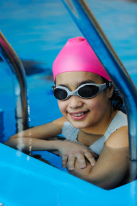 Girl in protective goggles leaves pool