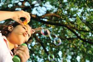 Girl making bubbles in nature