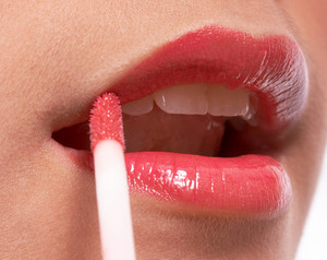 Girl Putting On Lip Gloss