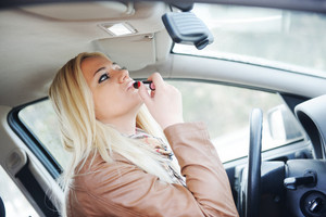 Girl putting on lipstick in car