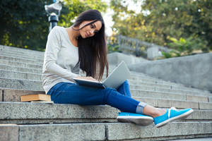 Girl sitting on the city stairs with laptop outdoors