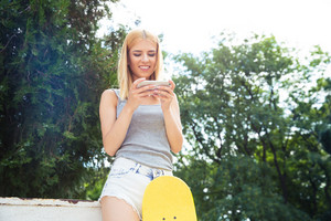 Girl with skateboard using smartphone