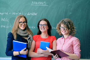 Girls with glasses holding books in front of blackboard