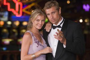 Glamorous couple standing inside casino