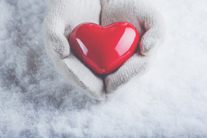 Gloved hands holding heart
