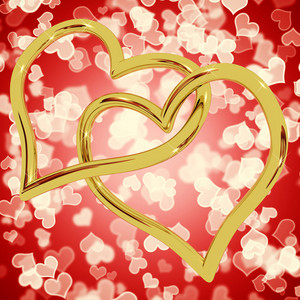 Gold Heart Shaped Rings On Red Bokeh Representing Love And Romance