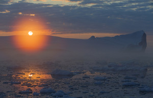 Golden sunset behind ice floes and a towering iceberg