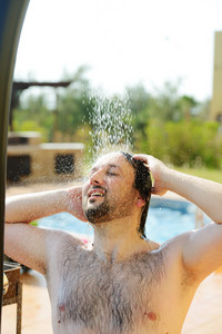 Good looking and attractive man with muscular wet body taking bath shower on resort pool outdoors