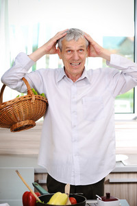 Good looking elderly man cooking  in kitchen