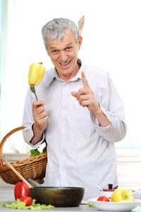 Good looking elderly man working in kitchen