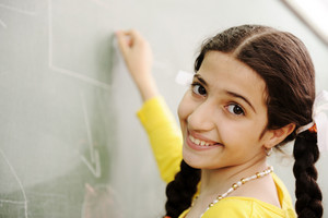 Gorgeous girl writing on classroom board