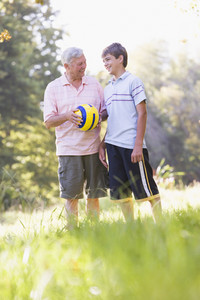 Grandfather and grandson at a park holding a ball and smiling