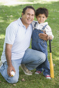 Grandfather and grandson holding baseball bat and smiling