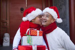Grandfather and grandson holding gifts dressed in holiday attire