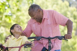 Grandfather and grandson on bikes outdoors smiling