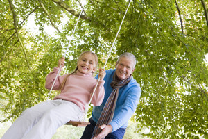 Grandfather pushing granddaughter on garden swing