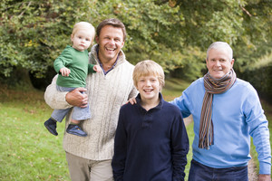 Grandfather walking with father and grandson along autumn path
