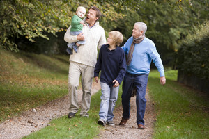 Grandfather walking with son and grandchildren along woodland path