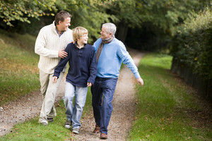 Grandfather walking with son and grandson along woodland path