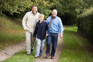 Grandfather walking with son and grandson through woods