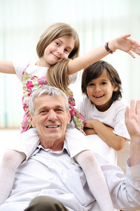 Grandfather with children, senior man at home with family