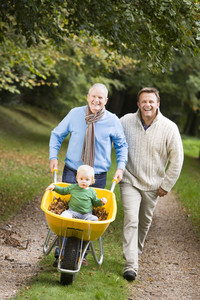 Grandfather with grandson and son pushing wheelbarrow along autumn path