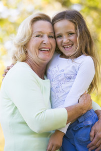 Grandmother and granddaughter outdoors and smiling
