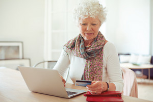Grandmother in front of laptop paying online using a credit card