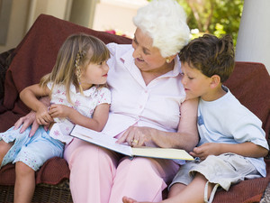 Grandmother reading a book to grandchildren