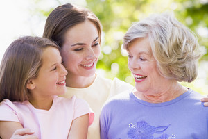 Grandmother with adult daughter and grandchild in park