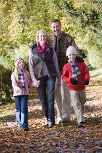 Grandparents and grandchildren on walk through autumn woods