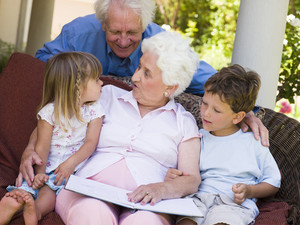 Grandparents reading a book to grandchildren