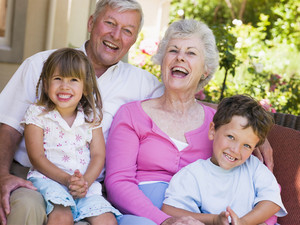 Grandparents sat on a sofa laughing with grandchildren