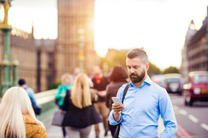 500px Photo ID: 128513715 - Handsome young man with smart phone on Westminster Bridge