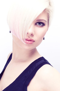 A beautiful and blond scandinavian young woman / model with creative hair style. Toned and natural retouched.